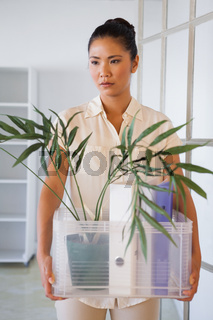 Fired businesswoman holding box of her things