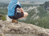 Hiker legs hiking in fall nature. Guy just relax on mountain top