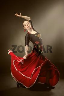 young woman dancing flamenco on black