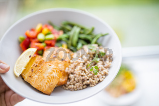 Female hand holding salmon and buckwheat dish with green beans