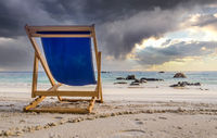 Dark clouds over deck chair at white beach in Ko Lipe, Thailand