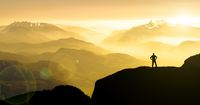 Spectacular mountain ranges silhouettes. Man reaching summit enjoying freedom.