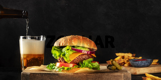 Burger and beer panorama. Hamburger with beef, cheese, onion, tomato, and green salad, a side view on a dark background with copy space. Selective focus
