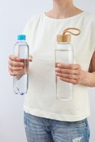The woman holds two bottles of glass and plastic of clean fresh water.