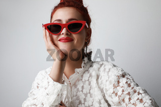 Beautiful woman in lace white dress wearing red sunglasses posing on gray background.