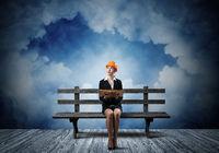 Beautiful woman architect sitting on wooden bench