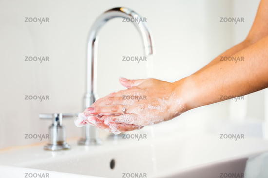 Woman washing hands with soap in bathroom with flowing water