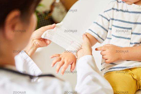 Kinderarzt wickelt Verband um Handgelenk von Kind