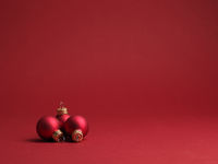 Three red vintage Christmas baubles on a red background
