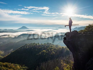 Man landscape photographer with photo gear on rock