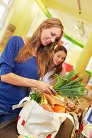 Frau packt Lebensmittel in Beutel