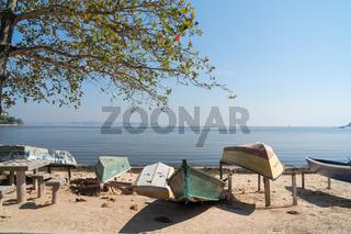 Row of small dirty fishing boats on the shore at the beach on Ilha de Paqueta Island, Rio de Janeiro.