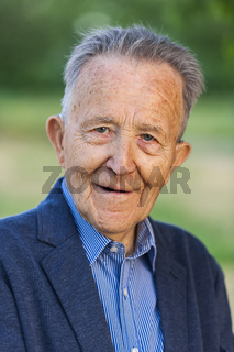 Portrait of an old man in a jacket looking kindly
