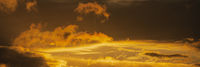 Panorama dramatic clouds illuminated rising of sun floating in sky to change weather