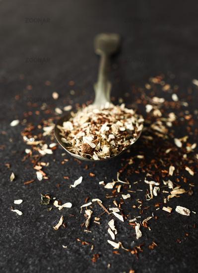 Organic tea blend on a rustic spoon, dark stone background