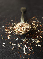 Organic tea blend on a rustic spoon, dark stone background