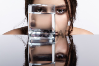 Girl hides her face behind a glass with water. Beauty portrait of young woman at the mirror table.