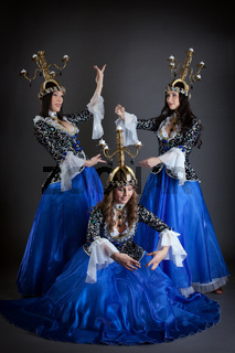Trio of oriental dancers with candelabras