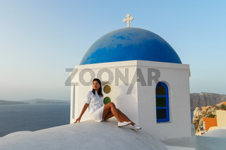 Santorini Greece, woman on luxury vacation Oia Santorini Island greece visit the white village with beautiful building overlooking the caldera