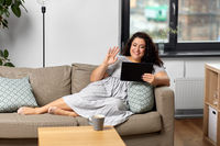 woman with tablet pc having video chat at home