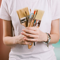 Closeup of woman's painted hands holding various paint brushes, selective focus
