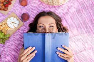 happy woman reading book at picnic in summer park
