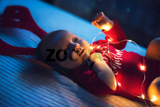 Little baby girl lie on the bed, christmas theme.
