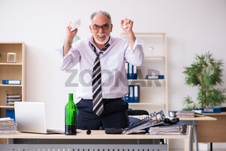 Old male employee drinking alcohol in the office