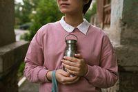 Female in pink sweatshirt holding sustainable metal eco bottle in her hands outdoors