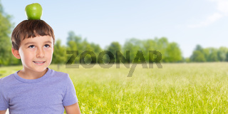 Child boy with an apple fruit on his head outdoors banner copyspace copy space healthy eating
