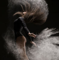 Woman in undrewear and pointe shoes in dust cloud