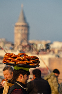 A Turkish man carries Simit on a tray on his head on the Galata Tower, Istanbul, Turkey