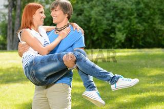 Teenage boyfriend carry girlfriend in his arms