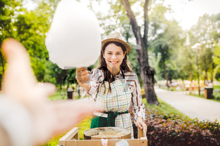photo theme small business cooking sweets. A young caucasian woman with an apron trader in the hat the owner of the outlet makes a candy floss, a fairy floss or a cotton candy in the summer park