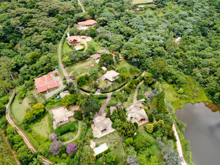 Aerial view of valley with lake, forest and villa in tropical country