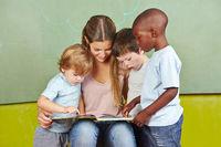 Kinder lesen Buch mit Kindergärtnerin