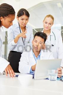 Arzt und Mitarbeiter arbeiten zusammen mit Tablet Computer