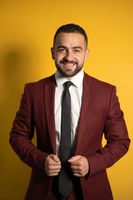 Young handsome man wearing amazing elegant burgundy suit looking on you smiling with hands holding a jacket isolated on yellow background. Men fashion concept