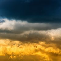 Thunderclouds and yellow-golden fluffy clouds illuminated by rays of sun