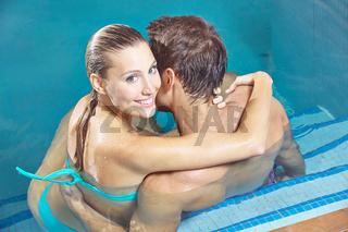 Zufriedenes Paar sitzt gemeinsam im Pool
