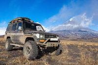 Lifted sport utility vehicle car Toyota Land Cruiser Prado on background eruption active volcano