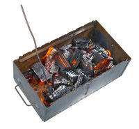 A metal rusty barbecue grill with coals and fire isolated