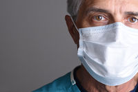 Closeup portrait of a mature male doctor wearing a surgical mask. Only partial face is seen with cop