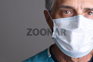 Closeup portrait of a mature male doctor wearing a surgical mask. Only partial face is seen with copy space on a gray background.
