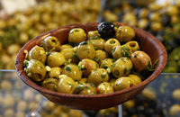 Green olives in wooden bowl on retail display