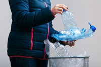 Woman collecting used plastic bottles and packagings in trash bin