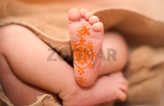 baby's legs are from under the blanket. On the leg painted a pattern marker.