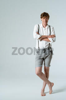 Stylish man in suspenders crossed his arms standing barefoot in full height in studio against white background. Charming dude
