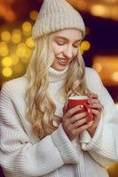 Young woman enjoying a mug of hot coffee
