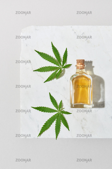 Medical marijuana oil and green cannabis leaves on a light grey marble background.